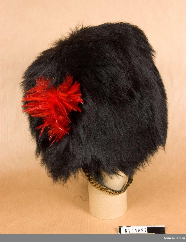 """Grupp C I.  BJÖRNSKINNSMÖSSA av svart, mjukt, kanadensiskt björnskinn, 300 mm hög, med röd fjäderplym, som sitter instucken på den högra sidan (kännetecken för Coldstreamgardet). Fodret är av svarta läderbitar som är fastbundna med bomullssnören. Hakrem av svart läder med mässingsfjäll, fastknuten till två krokar, som är fästade vid mössans insida. (Av tradition bärs mössan med remmen mitt på hakan). På en läderbit står 219144"""" och på en annan """"W"""" uppåtriktad pil """"D"""". Ovanför pilen """"S"""". I mössans botten finns firmans stämpel """"J. Compton son & Webb Ltd"""", """"7"""", """"London"""".  FODRAL av svart bomullstyg, till björnskinsmössa. Det är 550 mm långt och 350 mm brett. Fodralet är öppet på båda sidor och  stänges med ett insytt bomullsband. På fodralet finns stämplarna """"l Sg 209"""" och den andra stämpeln: """"l"""" ovanför """"86"""" som i sin är ovanför """"10"""" som i sin tur står ovanför """"130""""."""
