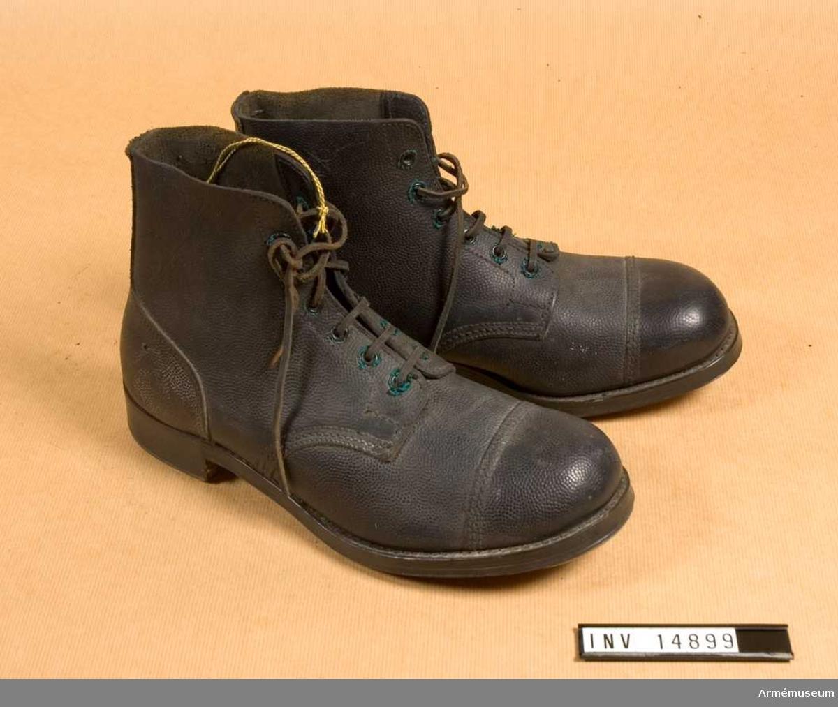"""Grupp C I. KÄNGOR, av grovt, svartfärgat läder med inskärning på framsidan och försedda med sex par järnringar, med vilka skorna snöres. Snörena är av läder. Sulor och klackar har järnbeslag. På sulorna finns stämplar: uppåtriktad pil """"8 M""""."""