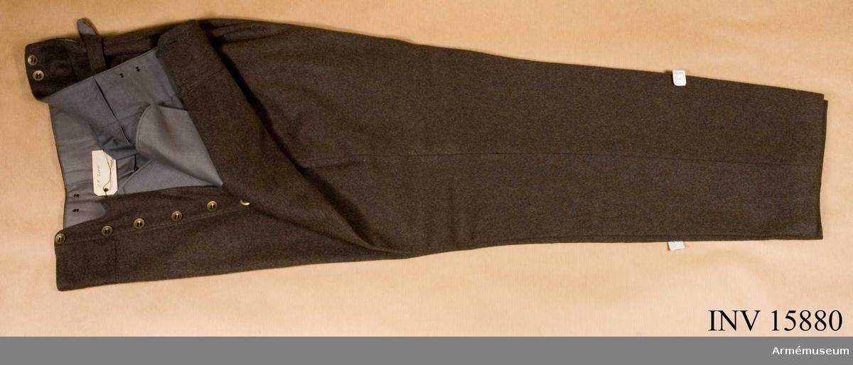 """Grupp C I. BYXOR av tjockt khakikläde, lång modell. Byxorna har fem fickor (två på framsidan, två på baksidan med två mässingsknappar, en  liten för klocka) sprund med sex knappar och för hängslen sex  knappar. Alla knapparna är flata mässingsknappar. På baksidan  spänntamp av kläde. Foder av grått bomullstyg. LITTERATUR: Enligt Handbuch för Uniformkunde Knötel - Sieg. Sidan 148. Fältuniform av khakikläde var infört i finska armén år 1927. Blyertsanteckningar på kortet: """"Användes vid skyddskåren med långa benkläder. Anhålles om sex stjärnor, två lejon"""". Ur fältuniform bestående av vapenrock och långbyxor. Deponerad från Arméförvaltningens intendenturdepartement modellkammaren."""