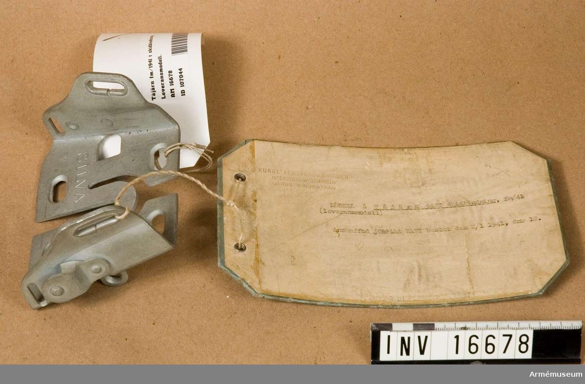 """Tvådelat tåjärn. Märkt """"Silva Patent V"""". Metalldelarna är av varmförzinkat stål. Modellapp: """"Kungl Arméförvaltningen intendenturavdelningen utrustningsbyrån. Modell av Tåjärn till skidbindning, fm/ 41 (leveransmodell)."""