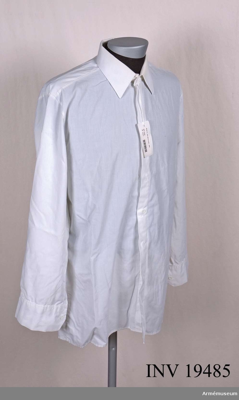 M7320-049000-4. Skjortan är tillverkad av vit skjortpoplin CO/PES. Skjortan har ej bröstfickor eller axelklaffar. Den tillverkas endast i en ärmlängd, normal. Manschetterna har två knapphål.  I ryggen finns två insyningar. Knäpps med 18 linjers knappar i plast. På kragens insida har skjortan en trekronorsstämpel, tillverkningsåret 1984, storleksangivelsen 40, och tillverkare HEAB/HESTRA AB.  Samhörande nr AM.19483-19494