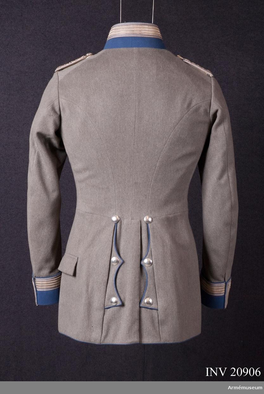 """Grupp C I. Ur uniform för officer vid Ostpreussiska Kyrassiärregementet Nr 3, Graf Wrangel. Armékåren 1918-1919.  Buren av G Hamilton. Av fältgrått tyg.  Åtsittande med midjesöm. Enradig med åtta knappar. På båda bakfickorna ett tvåuddigt lock, vartdera med tre knappar. På vänster sidan av rocken ett hål med lock för sabel. Foder (övre delen) av grått satintyg. Nedre delen är vit satin. Knappar, silverfärgade, 2 cm i diameter. På bak sidan av knapparna står """"extra finkvalitet""""."""" A & S"""" På bröstet fickorna och ärmuppslagen finns knappar av större modell, på  axlarna av mindre. Krage, upprättstående, med runda vinklar ljusblått tyg med ljusblå passpoal längs övre kanten samt  silvergalon, 3,5 cm bred (med svarta kantband, 0,5 cm breda). Kragen har tre hyskor och hakar samt är fodrad med grönt tyg. Passpoaler, ljusblå längs rockens främre kant och på de bakre fickornas lock samt omkring ärmuppslage. Ärmuppslag rakskurna, av ljusblått tyg, 8 cm höga med silvergalon, 3,5 bred. Galonen är kantad med svarta band, 0,5 cm breda. Längs uppslagens övre kant ljusblå passpoal. Under galonen finns två knappar. LITT  Das Deutsche Heer, Herb. Knötel, Band IV, sida 83: Regementet grundades år 1717. Arméenalbum I De deutsche armée in ihrer neuen Felduniformen, sid 3: Förändrades fält och freds uniformer infördes 1915-09-21. Sidan 17 och 18. Fullständig beskrivning av Kyrassiärernas vapenrock. Den tredje  bilden visar arméKyrassiärernas uniform. Deutschlands Armée in feldgrauer Kriegs- und Frieensuniform av militäramiraler Paul Cassberg, sid 5: Nya fält- och fredsuniformen infördes för tyska armén 1915-09-21: Bild 12: Modell av uniform för officer vid linjekyrassiärerna. Kyrassiärregemente nr 3 har färgerna vitt och blått enligt das Deutsche Heer. R Knötel, Band III, Kavalleri. Bild 69 och 70.Enl Granberg."""