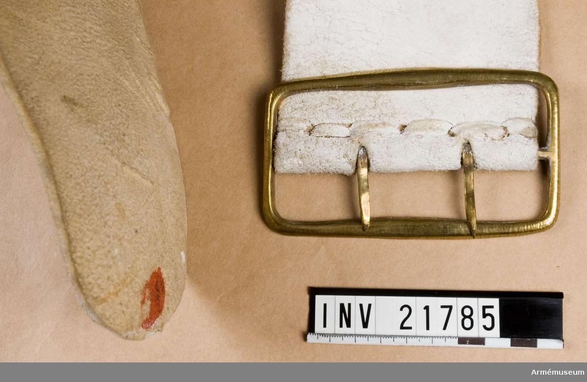 Grupp C I. Trumrem av vitfärgat läder med karbinhake. Ur uniform för spel, Hälsinge regemente. 1765-79. Består av rock, väst, knäbyxor, hatt, skor, strumpor, strumpe- band, halsduk, trumma med rem, trumstockar, livgehäng, huggare. Rem, bred, av vitt läder med karbinhake; gåva 1878 från Kungl.  Södermanlands regemente.