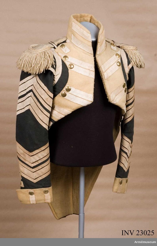 Grupp C I. Ur uniform för spel vid Svea Livgarde 1812-16. Består av frack, epåletter, väst, knäbyxor, huvudbonad,  plym, skor, damasker, spännhalsduk, gehäng, rem till huggare, trumma, bärrem, trumstock. Mörkblå frack med gula bröstrevärer, vita redgarnsknapphål och redgarnsdekorationer.