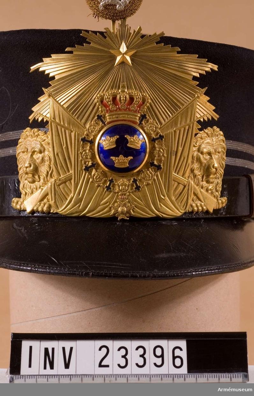 Samhörande nr är 23395-8, mössa, vapenplåt, pompong, knapp. Vapenplåt m/1865 för löjtnant vid Första livgrenadjärreg. Grupp C I.