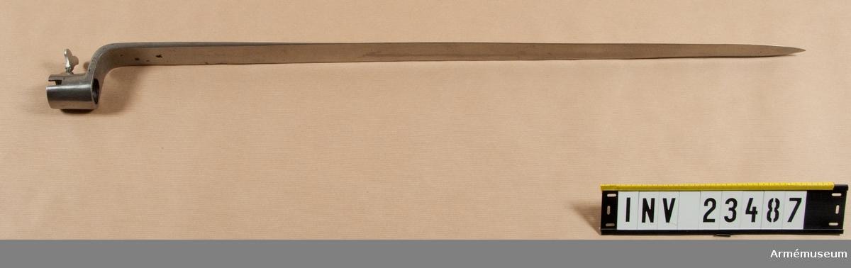 Grupp E II.  Hylsa till bajonett, infanteri. Bajonetthylsan är 45-46 mm lång. På översidan har hylsan en 16  mm lång, baktill 7, framtill 6 mm bred urtagning för kornet. På  V sida omkring 9 mm ovanför underkanten är en skarpkantig, 12 mm  bred klack fastlödd med koppar. Den genombrytes av ett gängat  hål, i vilket en vingskruv är insatt.   Klingan har nedtill rektangulärt tvärsnitt och en bredd av 33  mm, men armen blir bredare mot hylsan som har yd: 33 mm. I övrigt är klingan till större delen eneggad, men eggen börjar ganska långt ovanför armen. Omkring 190 mm bakom udden får klingan egg även å ryggsidan. Nedtill på klingans insida finns ett inslaget P och siffran 5, men längre upp är en femuddig stjärna inslagen. Litet ovanför armen genombrytes klingan av ett hål med omkring d:3 mm. När bajonetten påsättes inpassas kornet i urtagningen i  bajonetthylsan och sedan vrider man åt vingskruven, vars ände då trycker mot pipan i den ovan omtalade urfilingen.   Påsatt sitter bajonetten till vänster om geväret med den längre eggen vänd uppåt. Den på bajonetten inslagna femuddiga stjärnan återfinns på andra  bajonetter, t.ex AM 1932:4077 och 4085, men även på värjklingor,  såsom AM 1932:9900.