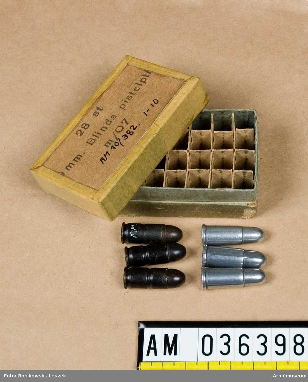 Grupp E V. Pappask med tre blinda patroner och tre avgjutningar av 9 mm patron för pistol m/1907.