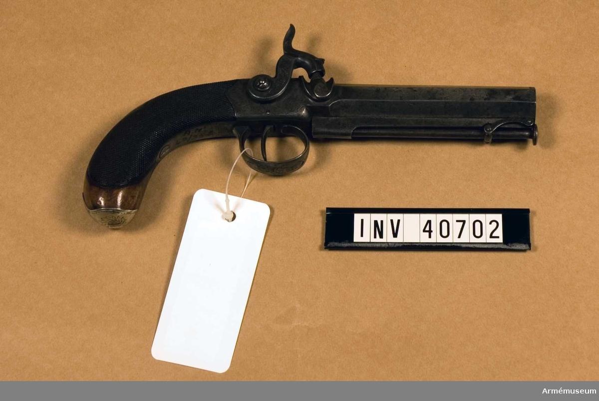 """Grupp E III.  I par med pistol 40701. C:a 1820 tillverkade av D Egg, London. Birminghams kontrollstämplar. Pipan är åttkantig, på översidan signerad """"D.Egg. London"""" Låda, hane och varbygel prydda med etsade bladmotiv. Hanens övre del föreställande en fisk. Kolvkappan tillverkad av silver med graverat mönster. Pistolerna är märkta med två av Birminghams kontrollstämplar. På en av pistolernas laddstock saknas främre delen. Tillverkningsnummer saknas."""