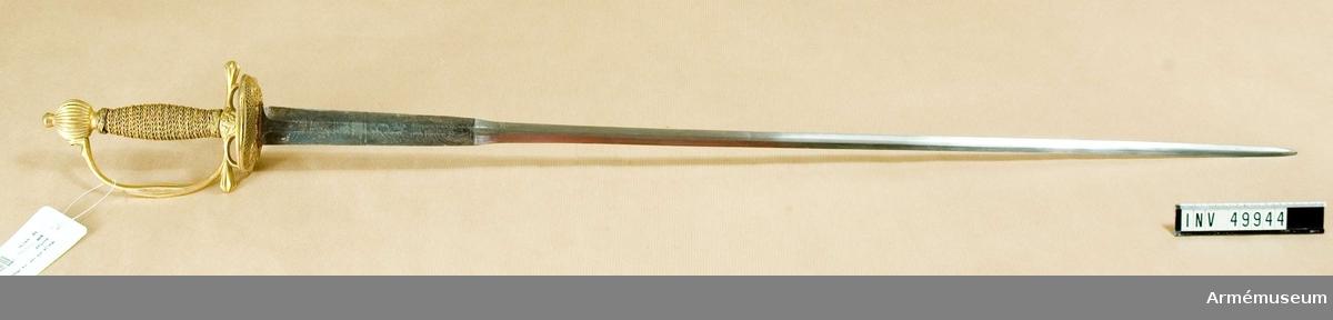 """Grupp D II.  Klingans bredd 19 cm från fästet är 15 mm. Klingan har colichemardeform och har flata åsar. På det bredare partiet är den blånad, etsad och förgylld i ornamentet och på kvartsidan Gustaf III:s krönta namnchiffer. Orneringen är synnerligen grovt utförd. Fästet är """"ett franskt fäste"""" av starkt förgylld mässing. Knappen är rätt låg, har spetsovalt tvärsnitt samt är prydd med vertikala räfflor. Nitknappen är låg och har formen av en med avrundad bas försedd stympad kon. Halsen är instrypt och längs nedre kanten prydd med en rand. Kaveln är spolformig, har rektangulärt tvärsnitt och är lindad med förgylld tråd, som ser ut att vara av silver. Upp- och nedtill omges kaveln av en platt flätning av snodd tråd, men i övrigt är den lindad med två grova och en smal tråd, alla sammansnodda av två parter. Den ena grova tråden och den fina är snodda åt samma håll, den  andra grova är snodd åt motsatt håll. Parerplåten har på över- och undersidan på mitten ciselerade  ornament och är i övrigt prydd med fyrkantiga hål. Parerstångens  ändar är kraftigt förtjockade och liksom handbygelns mitt med  sexkantigt tvärsnitt och prydda med räfflor. Handbygelns övre  del är enkelt ciselerad och dess övre ände är medelst en skruv  fäst vid knappen.Värjan har burits av kaptenen vid Upplands regemente, Elgenstierna, född 1738, avsked 1776. Samhörande nr är 49944-5, värja, balja."""