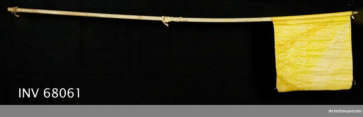 Duk: Tillverkad av enkel, citrongul sidentaft, fållen lagd åt dukens utsida. Duken fäst med en rad tennlickor på ett gult, mönstervävt band.  Dekor: Saknas.  Stång: Tillverkad av trä, vitmålad. Holk finns, men ej spets.  Mellan 690-710 mm från dukens fäste är en ljus skinnremsa instucken, ca 645 mm lång, från nedre änden mätt. 450-650 mm från fästet är en brun läderrem instucken, ca 550 mm lång.
