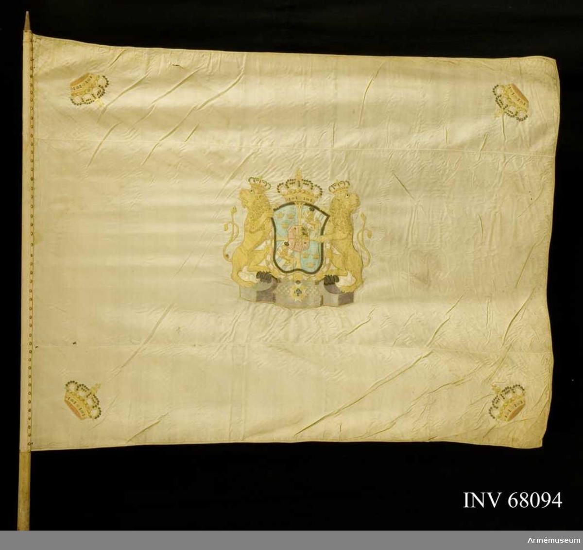 Duk: Tillverkad av vit sidenkypert, sydd av tre vertikala våder. Duken kantad med vitt mönstervävt band. Duken fäst vid stången med ett likadant band och en rad tennlickor.  Dekor: Stora riksvapnet, Holstein-Gottorp, applicerat och broderat lika på båda sidor. Skölden guldkantad, behängd med serafimerkedjan, krönt med sluten kunglig krona i gult silke, foder i rött silke och pärlor i silver. Sköldhållare i dubbelsvansade lejon med slutna kronor. Postament i grått silke. I dukens hörn slutna kronor.   Stång: Tillverkad av vitmålad furu. Saknar spets och holk. Avsågad.