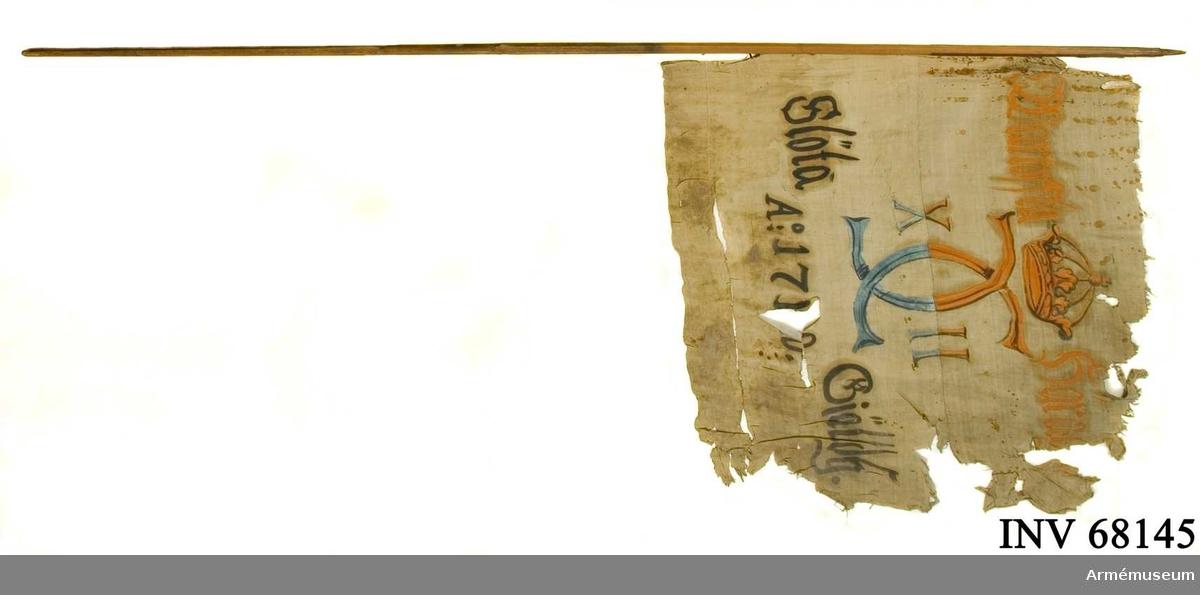 Duk: Tillverkad av enkel linnelärft, sammansydd av tre våder. Fäst med en rad järnnagel på en liten skinnremsa.   Dekor: Målad i mitten. Omvänt lika på båda sidor, Carl XII:s namnchiffer, krönt med sluten krona, dubbelt C på ömse sidor om vilket X - II, i gult och brunt på den övre våden ochblått och svart på den nedre. Text på ömse sidor om chiffret, upptill i gult och nedtill i svart. Under allt detta text i svart.  Stång: Tillverkad av trä. Stången är åttkantig nertill. Greppet avsmalnande upptill.