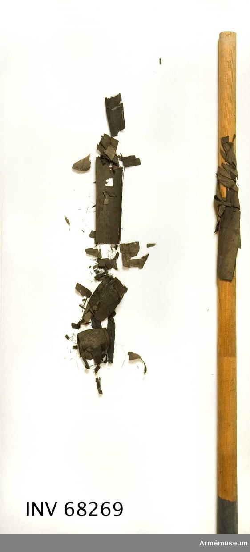 Fanstång av svartmålad furu. Åttkantig med slätt, rundat handgrepp. Upptill fragment av svart sidenduk. Stången omålad under duken. Märkt: ST 10036, målat nedtill.