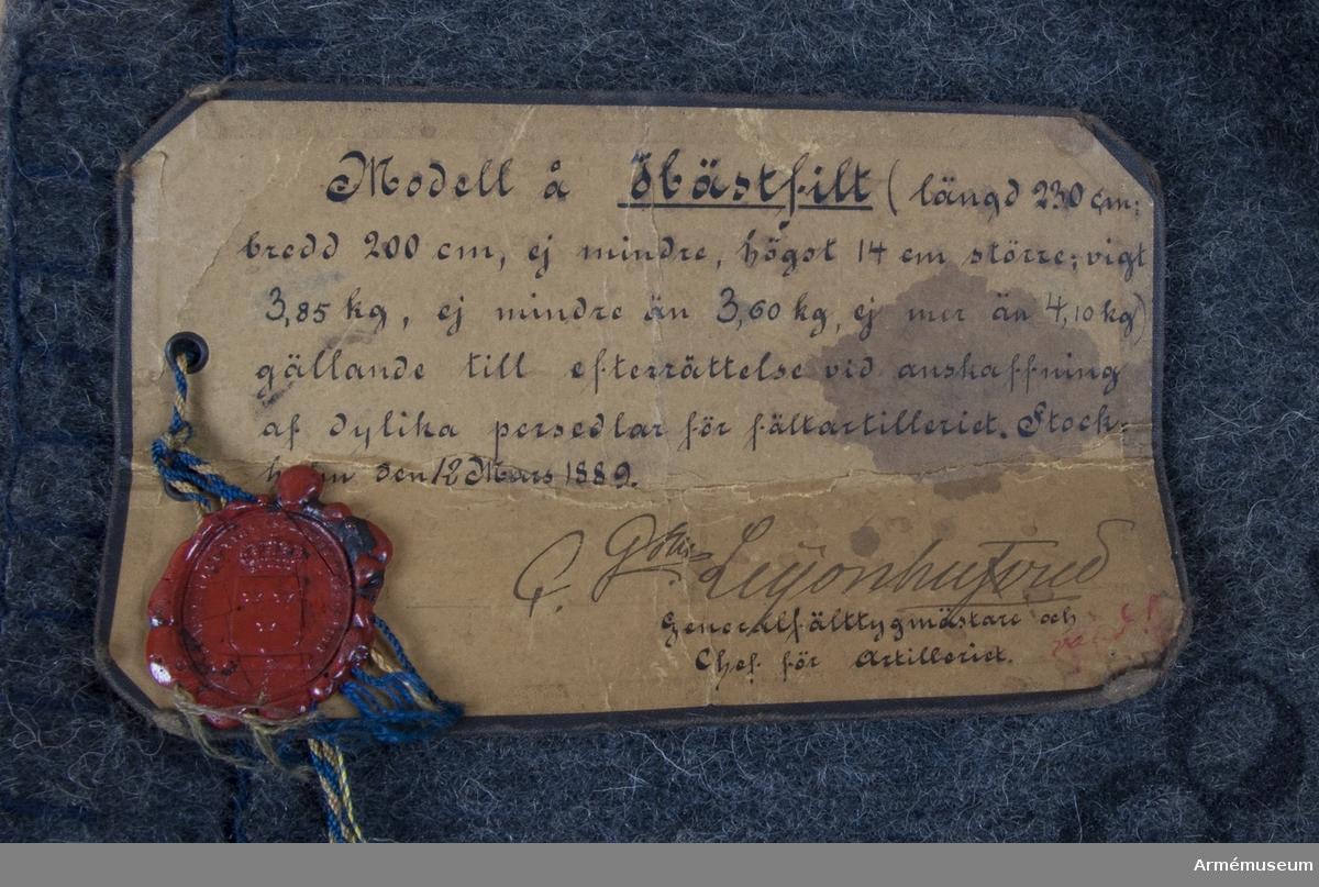 Grupp K: I. Text på modellapp: Modell å Hästfilt (längd 230 cm, bredd 200 cm, ej mindre än 3,60 kg, ej mer än 4,10 kg) gällande till efterrättelse vid anskaffning af dylika persedlar för fältartilleriet. Stockholm den 12 Mars 1889.
