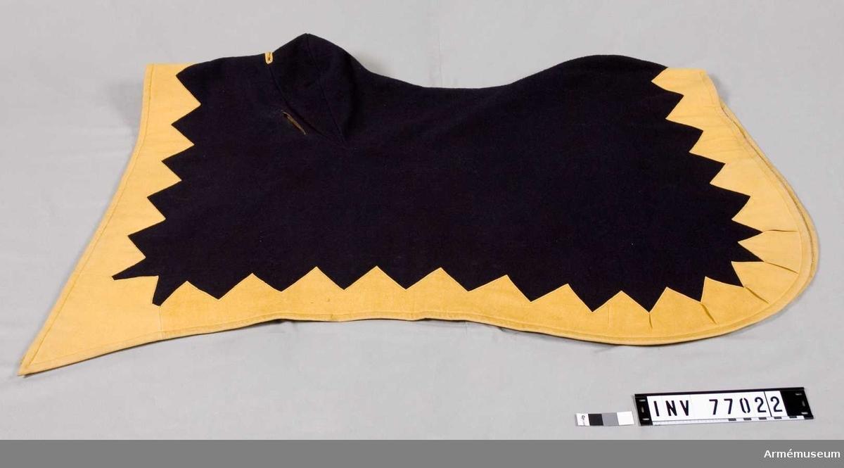 Grupp K I. Regemente Husarregementet Carl XV. Land S. Tillverkad av blått kläde med taggig kant av gult kläde. Rundade hörn.