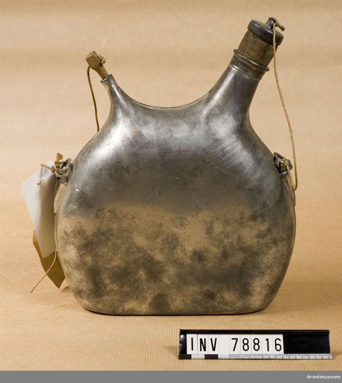 Grupp I.III. Av bleckplåt med två öppningar, en liten för luft och en större som har kork. Flaskan har två ringar att koppla till till axelgehänget. Klädesfodra saknas. Fältflaskan rymmer två liten.