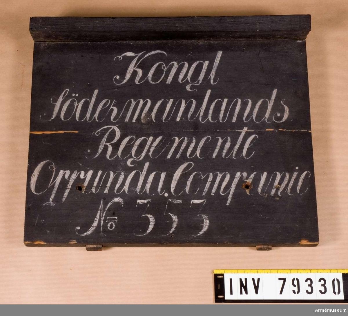 Grupp L. En svartmålad rektangulär trätavla med regnskydd. Vitmålade bokstäver:Kongl. Södermanlands Regemente Oppunda Companie No 353 ( på gamla etiletten står 355 likaledes i katalogen) på fem rader.