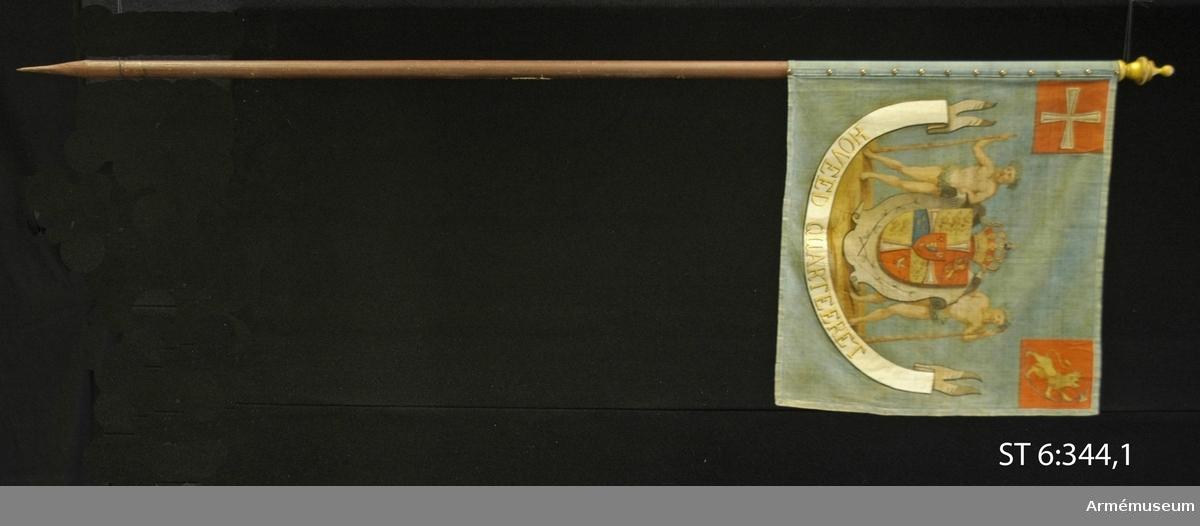"""Duk av blått bomullstyg. Motiv av danska riksvapnet med vildmän som sköldhållare. I övre hörnet på stångsidan är dannebrogen målad, i yttre Norges vapen. I en båge under riksvapnet ett vitt språkband med texten """"HOVEED QUARTEERET"""" skrivet i guldfärg. Den ursprungliga texten i språkbandet är: ANDET OPLANDSKE NACIONAL INFANTERIREGIMENT, men detta har blivit övermålat. Duken är kantad med ett centimeterbrett linneband. Duken är lindad kring stången och fäst med tännlikor, spikade på ojämnt avstånd genom ett blått linneband. Stången är rund, jämntjock och brunmålad. Enligt äldre beskrivning ska stången ha en 15 cm lång spetsig metallskoning men i senare tid har stången skarvats med en förlängningsbit, ihopfäst med pappersremsor, troligen för utställningssyfte. Spetsen är en svarvad, förgylld träknopp."""