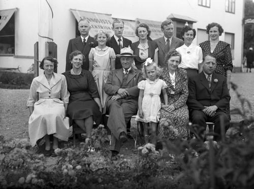"""Familjen Sahlsten utanför Richard Sahlstens affärsfastighet Centrumhuset i Munkedal, 1949-1950 Personerna är (stående från vänster) Tage Eliasson (gift med Viola), Gunnel Eliasson (dotter till Tage och Viola), Sune Eliasson (son till Tage och Viola), Millicent """"Mimmi"""" Sahlsten (dotter till Rickard), Evald Rickard """"Rick"""" Sahlsten (son till Rickard), Britt Sahlsten (gift med Rick) samt Stina Sahlsten (född Jansson, gift med Erling). Sittande från vänster: Gulli Lundquist (född Sahlsten, dotter till Rickard), Viola Eliasson (född Sahlsten, dotter till Rickard), Rickard Sahlsten, Lisbeth Sahlsten (dotter till Erling och Stina), Hilma Olena Sahlsten (gift med Rickard) samt Erling Sahlsten (son till Rickard och bedrev taxirörelse fram till 1970-talet)."""
