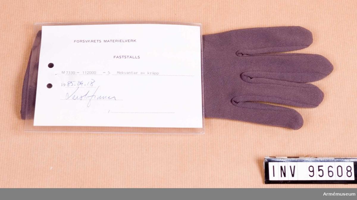 """Vidhängande etikett: """"Försvarets materielverk Fastställs M 7330-112000-5, Mekvantar av kräpp, 1985-09-18 (oläslig underskrift)""""."""