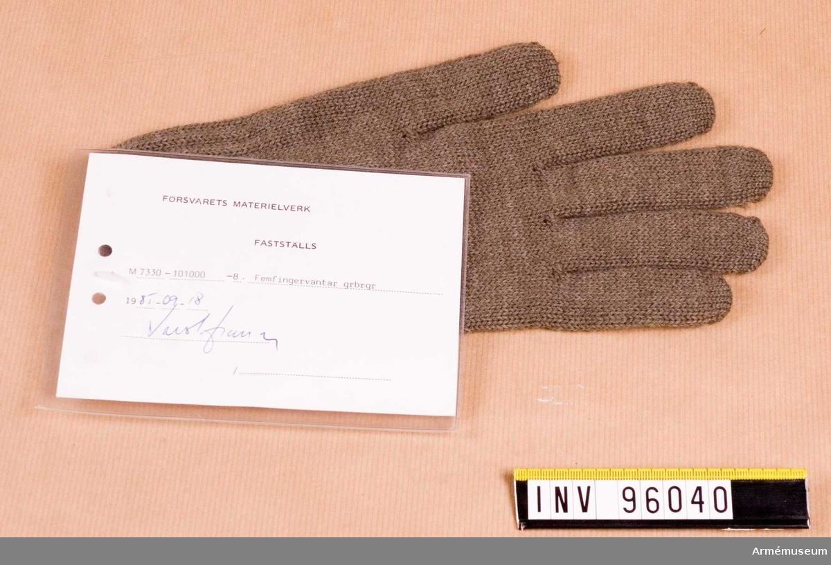 """Vidhängande etikett med text: """"Försvarets Materielverk, Fastställs, M 7330-101000-8, Femfingervantar grbrgr, 1985-09-18, (oläslig underskrift)"""""""