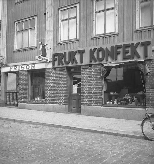 """Text till bilden: """"Skylt v. Kallins Fruktaffär, f. Klint & Tinggren. 1946.08.15""""."""