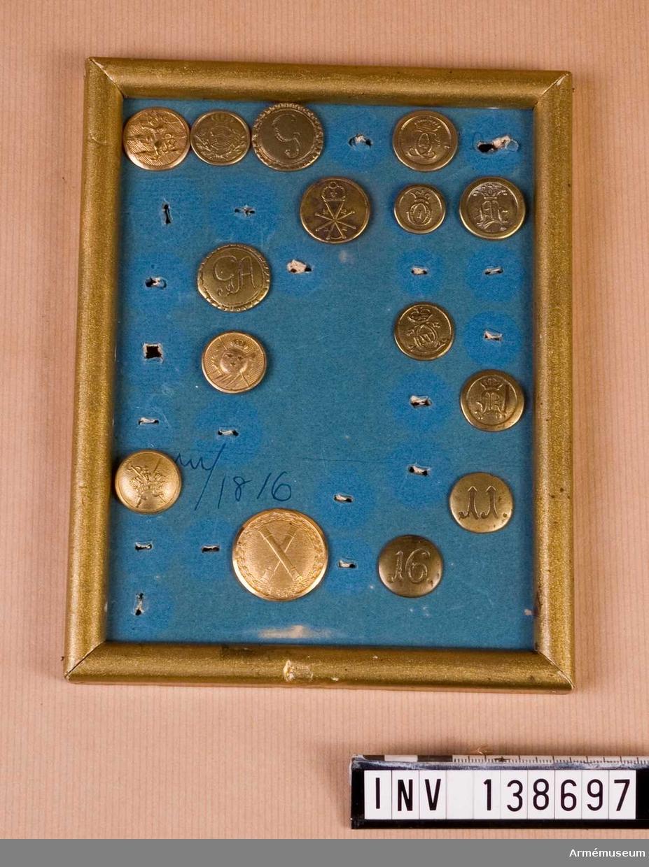 Knappar med Kungl. monogram och regementsnummer, från tidigt 1800-tal. 15 st monterade i ram. GA, C 14, C XV, O II, 2 regnr, 6 st div.