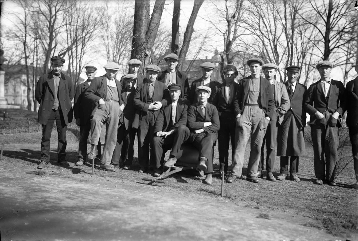 En samling män, kanske parkarbetare. Två av dem sitter på en vält.