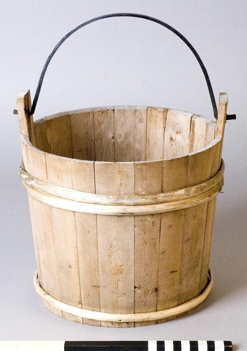 Spann av trä med smitt handtag av järn. Spannen utförd i laggteknik och hålls samman med två band av eneträ.