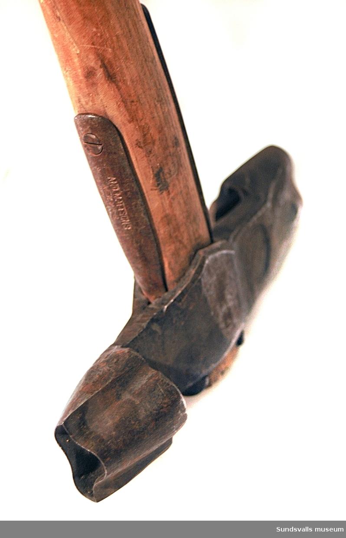 Märkyxa med träskaft. Huvudet mäter 19 cm och har oregelbundet formade huggmärken. Användes av Nyhamns AB.
