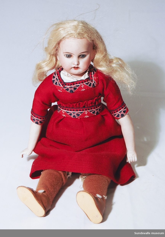 Flickdocka med huvud och armar av porslin. Klädd i röd klänning med mönstrade band kring hals, ärmar och midja. Linne och underbyxor, virkad underkjol, bruna strumpor och skor, samt ett rött hårband .