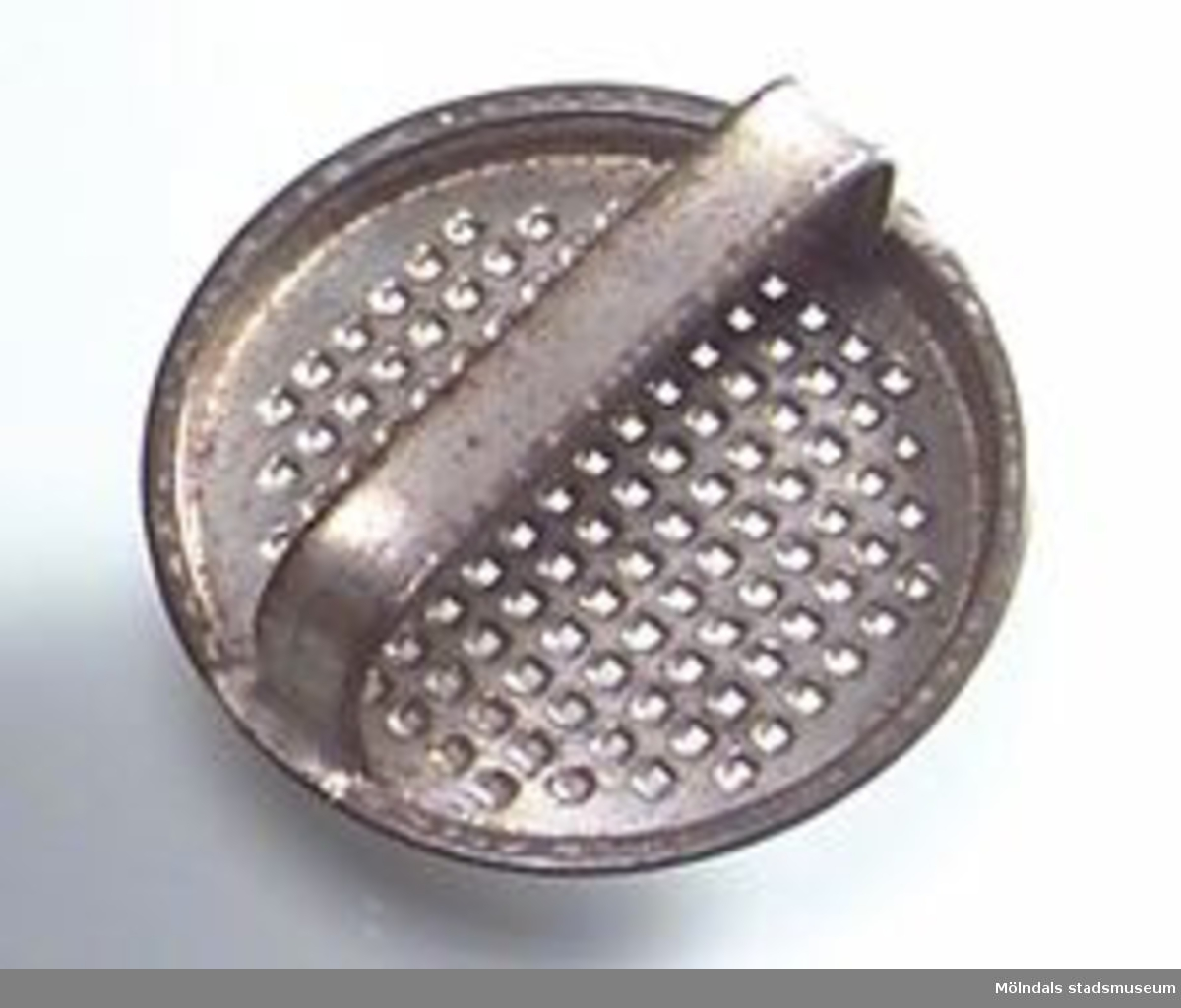 Rivjärn av bleckplåt, utformat som ett runt lock med ett handtag över.