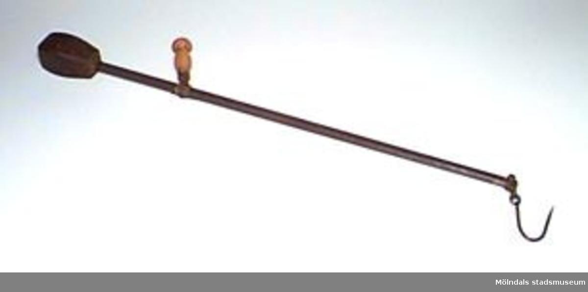 Handvåg med en hävstång med fast kula av järn som motvikt. På stången finns en rörlig hylsa med trähandtag.Anna Andersson är givarens moster.