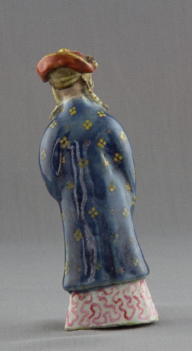 Figurin av porslin, glaserad i många färger. Huvudbonad i gult, svart och rött, blå överklädnad med dekor av guld, röd/vitmönstrad underklädnad. Figuren håller något gult i varje hand.