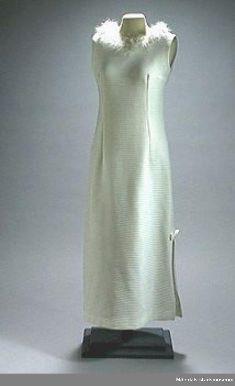 Ärmlös, vit klänning av maskinstickat tyg som är smalt ribbad på tvären. Den kraglösa halslinningen är kantad med vitt fjäderdun. Halvmeter lång dragkedja i ryggen.400 mm lång slits på vänster sida. Vid slipsstoppet är en rosett fastsydd.Livlängden på klänningen är 500 mm. (Till klänningen hör broschen MM02325).