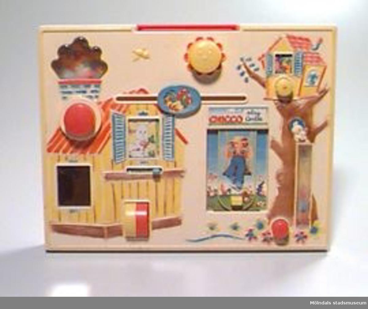 """Rektangulär plastlåda med utdragbart bärhandtag upptill. På lådans stora fasad (30x38 cm) finns ett antal knappar och reglage kopplade till """"fönster"""" i lådan. Där händer det saker när reglagen rörs. Kulor rullas upp, ljud hörs, bilder byter plats etc.Motivet är en lantgård med djur och små byggnader. Lek- och aktivitetsfrämjande för yngre barn.Märkt med tusch på baksidan med: Lille skutt 1990.Gåva av Katrinebergs daghem."""