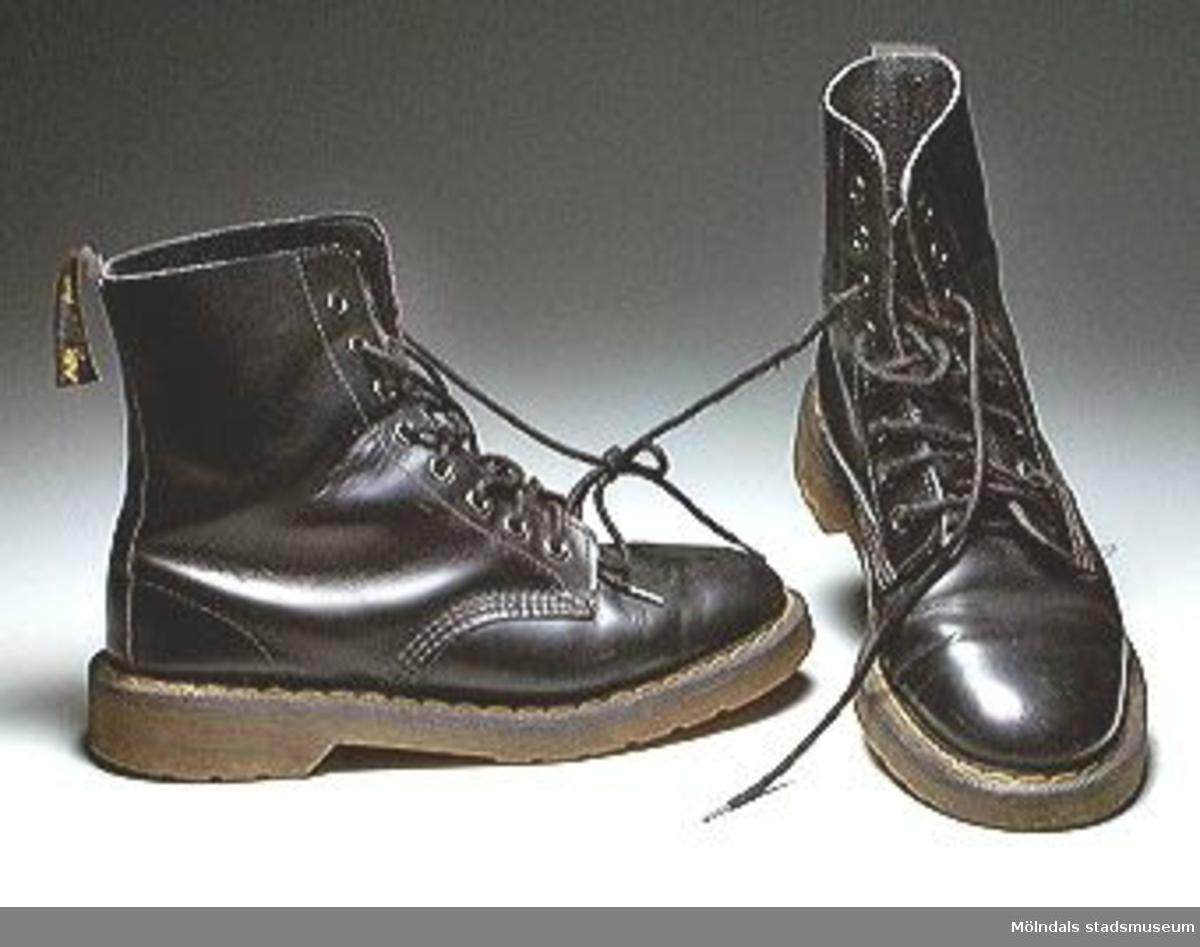 """Svarta Dr. Martens kängor. Märkta: Air soles, cushion. Storlek 5. Till utställningen """"Krinoliner och kortkort"""" (5 feb. 1995 - 26 nov. 1995)."""
