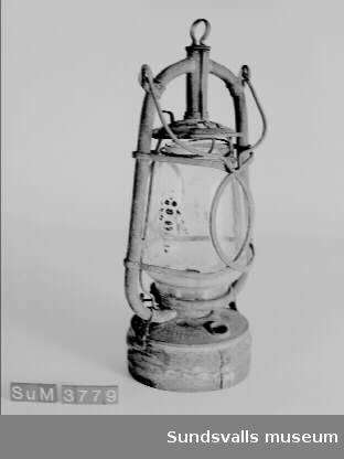 Fotogenlykta med glaskupa och handtag. I glaset finns ett mönster i form av ett bi. På en plåt står texten 'G.J. Bergman & Co FENIX No 1'. Lyktan användes på den år 1875 invigda 'Lindgrenska Arbetsinrättningen', sedemera pensionärshemmet Holmgården, Sundsvall.