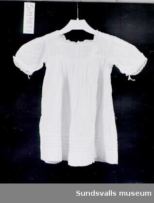 Vit klänning i skirt bomullstyg med invävt rut- och prickmönster. Spets runt ärmslut och vid halsöppningen. Knäppning bak med två knappar och en tryckknapp. Blombroderi i vitt på bröstet och fyra sydda veck på kjolen.