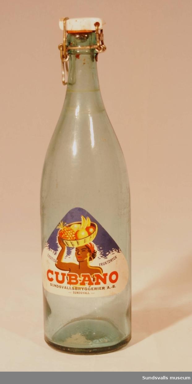 En läskedrycksflaska med patentkork från Sundsvallsbryggerier AB. Flaskan är tillverkad i blåtonat glas och är försedd med en trekantig etikett med texten 'EXOTISK FRUKTDRYCK CUBANO, SUNDSVALLSBRYGGERIER A.-B. - SUNDSVALL -'.