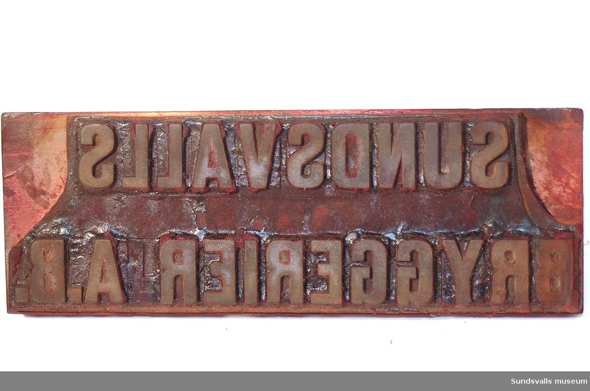 Stämpel med texten 'SUNDSVALLS BRYGGERIER A.B.'. Hantag och platta av trä, bokstäverna av gummiliknande material. Ovanpå sitter en liten metallskylt med texten 'ELIS ÅBERGS STÄMPELFABRIK TEL. SUNDSVALL 12800'. Stämpeln bär spår av röd färg.