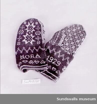 Ett par bruna mönsterstickade tumvantar med beige mönster i form av bl.a. stjärnor, hjärtan och texten 'MORA 1929'. Enligt anteckning ska vantarna vara tillverkade i tvåändsstickning.