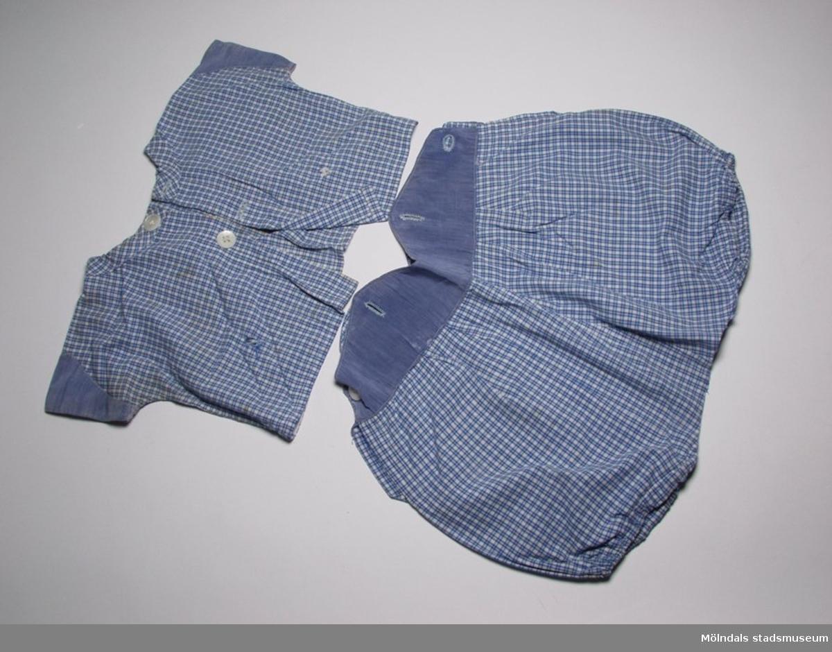 Tvådelad lekdräkt i smårutigt bomullstyg i blått och vitt. Korta ärmar och ben. Blus (:1) bredd: 350 mm, längd: 220 mm.Byxa (:2) bredd: 370 mm, längd: 290 mm.
