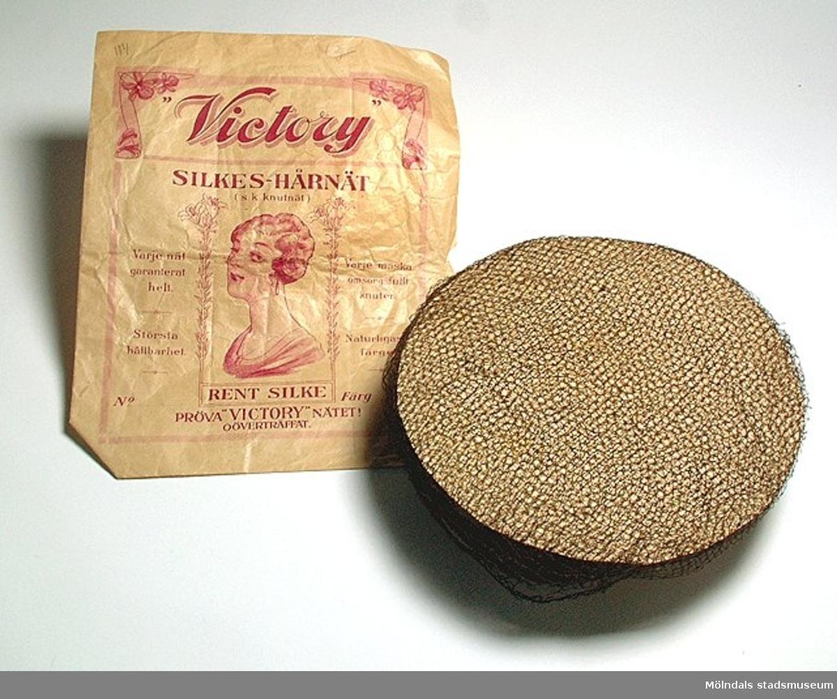 """Hårnät som sitter uppspända på en rund pappskiva.Förpackning """"Victory"""" silkeshårnät (MM 03767:2) hör ev. ihop med hårnäten."""