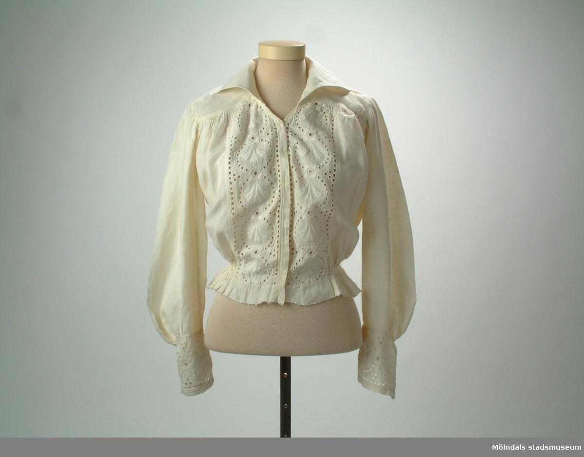 Blusliv i naturvitt linne med engelsk brodyr framtill och runt handleder. Bluslivet är troligen avklippt från en klänning.