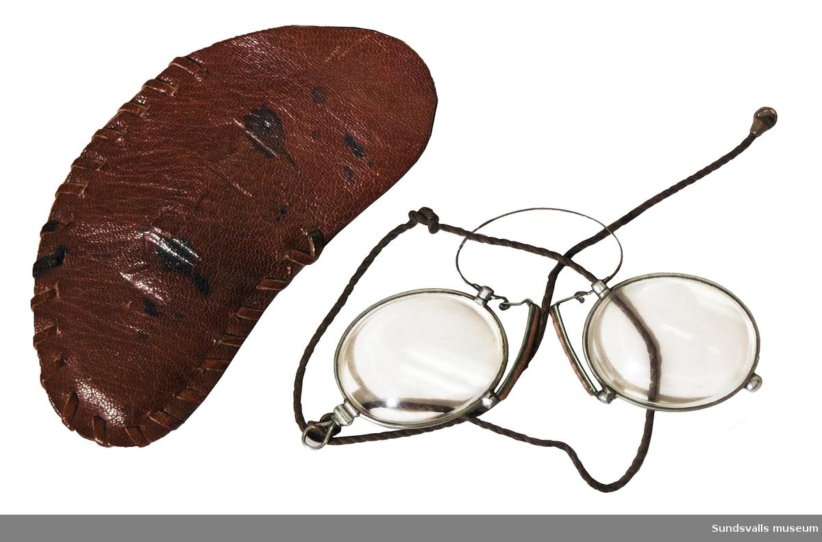 Pincené med fodral. Ögla med snodd. Fodral i formsytt, brunt läder med präglat monogram 'MR-M', samt en blomma på motsatta sidan. Fodralets längd är 11,5 cm.