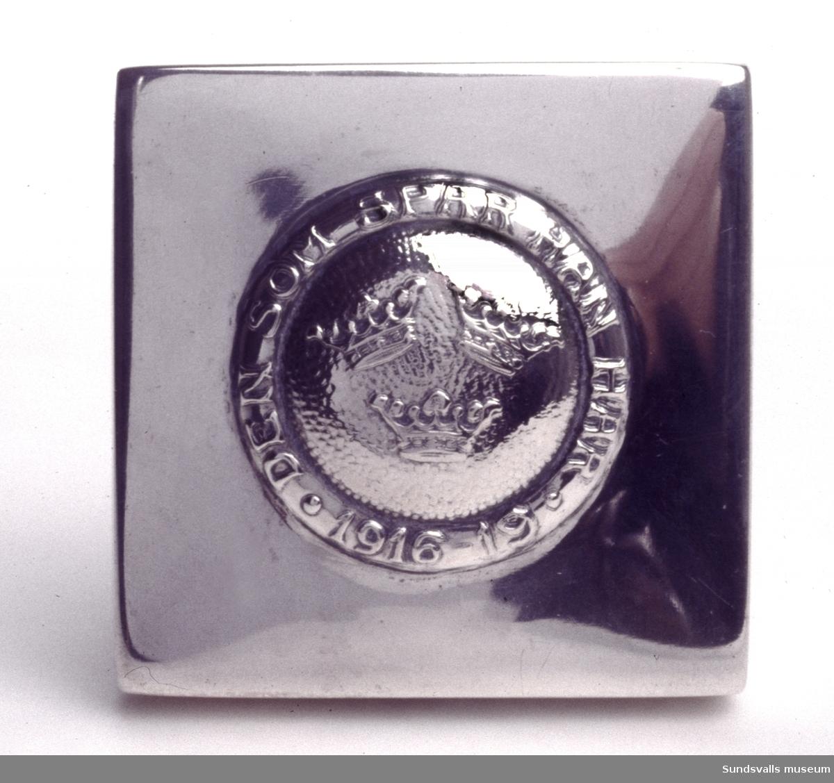 Sockerdosa i silver. Kvadratisk form med ciselerad dekor i form av tre kronor omgivet av texten 'Den som spar han har 1916-19'. Förgyllning invändigt. Stplr: 'E Sm H 1918', även på locket.