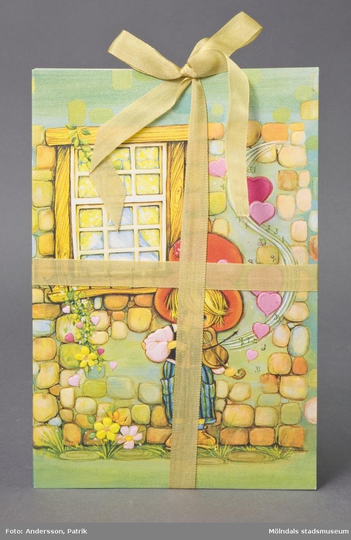 """3 st dubbla brevkort av papp med linnestruktur, ihopbundna med guldfärgat sidenband.På framsidan; målning av pojke i röd, hög hatt, med fiol, framför stenvägg med ett fönster. Med i bilden finns också lite gräs, blommor och hjärtan. Ur fiolen kommer noter och fler hjärtan. Detaljerna är präglade i upphöjd relief. På insidan finns plats för att skriva hälsningar, gratulationer eller liknande. Text på baksidan anger: """"Rust Craft, 470800, Copyright, Printed in England"""". Motivet är tryckt i England, men tillverkning har skett på Papyrus, Mölndal."""