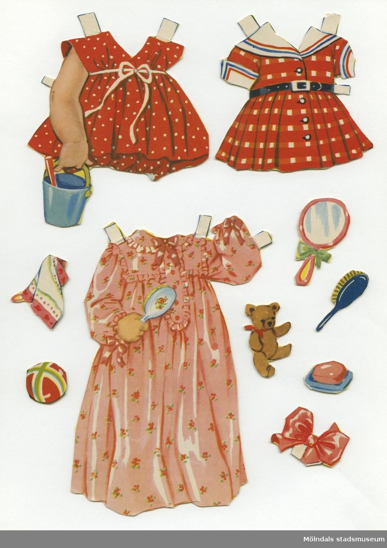 """Pappdocka med kläder och tillbehör. Docka och kläder är märkta """"Lena"""" på baksidan - dockans namn. Dockan föreställer ett litet barn, med blont hår och blå ögon, iklädd vitt linne, underbyxa och röda skor. Två lösa ansikten gör att man kan byta dockans ansiktsuttryck från allvarlig till glad eller ledsen. Garderoben består av fyra klänningar, hängselbyxor, nattsärk, mössa, halsduk, samt ytterkläder med tillhörande huvudbonad. Dockan har också tillbehör, såsom haklapp, spegel, hårborste och leksaker. Dockan förvaras, tillsammans med """"Lillan"""" (MM 04637), i ett ihopvikt silkespapper med texten """"Ljungsko, Kvalitetsko""""."""