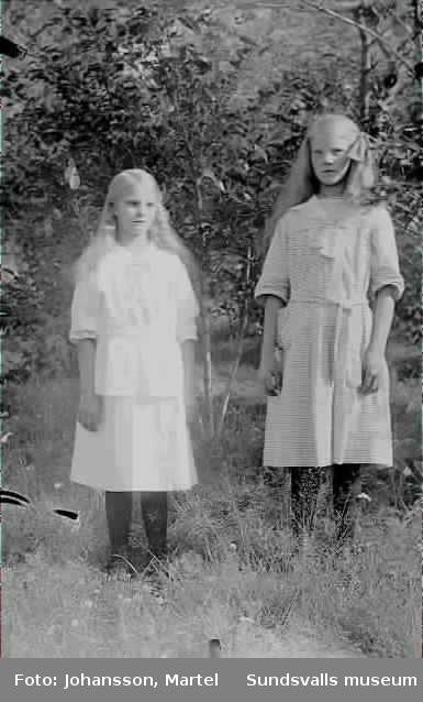 Två flickor i fina klänningar ute i gröngräset.